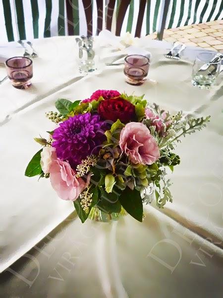Esküvői asztaldísz színes virágkból, dáliával, gömb vázában