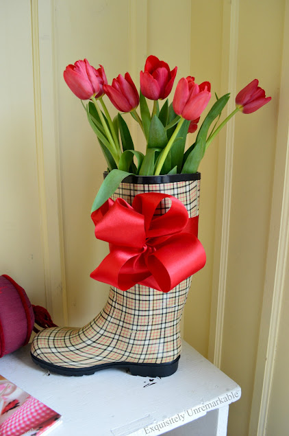 Rain boot with flowers and bow on bench