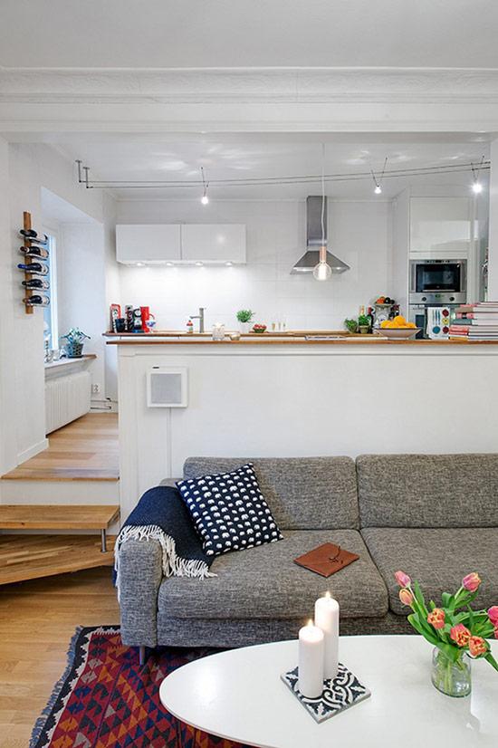 Bếp hiện đại màu trắng với rất nhiều đèn và phòng khách với ghế sofa nệm và gối tựa êm ái.