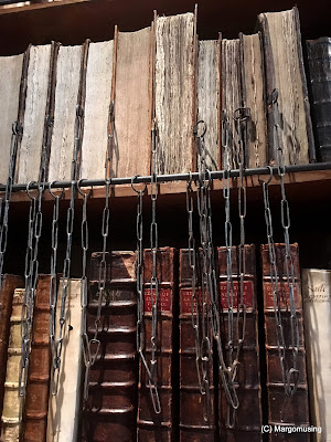 two shelves of books,the upper ones shelved spine in, and chained, the lower ones shelves spine out