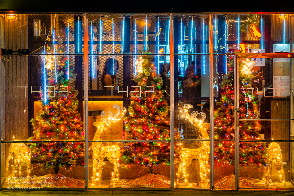 a photo of a restaurant window in new york with christmas decorations