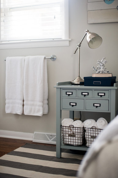 The towel rack against the wall works great next to the blue nightstand.