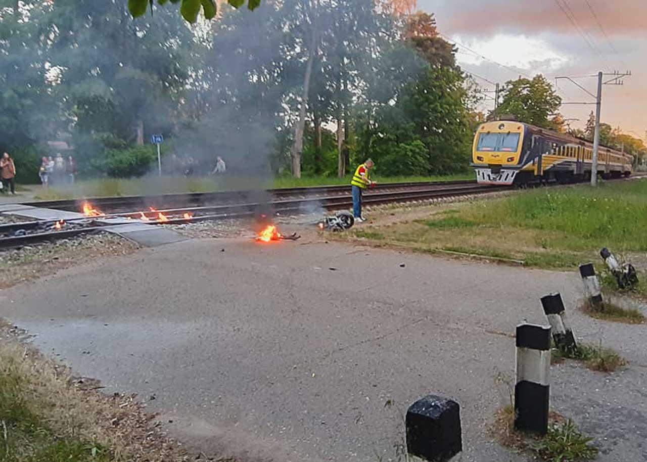 Sadragātā motocikla detālas deg pie dzelzceļa sliedēm