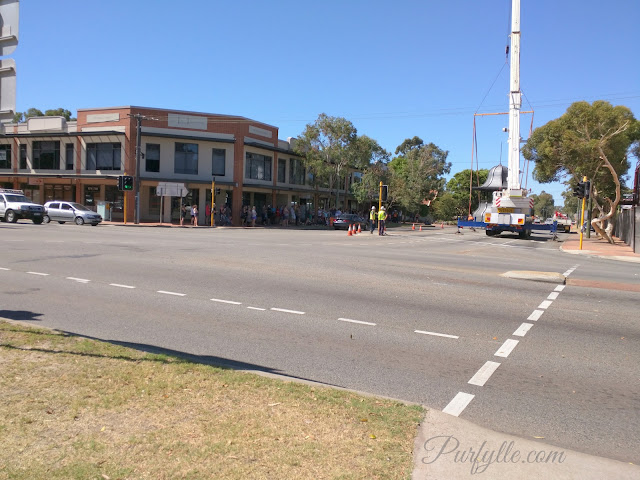 Locals gather on street corners to observe and photograph the historic moment of Guildford Hotel belvedere being restored