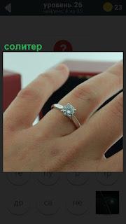 Ювелирное изделие солитер в виде кольца на пальце у женщины