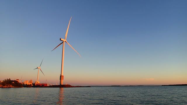 Kaksi tuulivoimalaa satamassa iltaruskossa