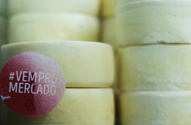 um adesivo encontrado numa vitrine de uma loja de queijo convida os visitantes à irem ao mercado; vem pro mercado; diz o adesivo