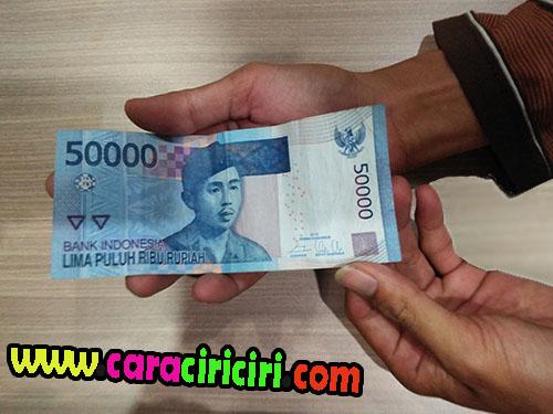 memegang uang 50 ribu