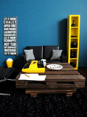 Modern one-twelfth scale miniature lounge in teal, yellow and black, with a typewriter sitting on a pallet coffee table.