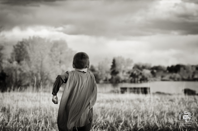 awesome black and white image of a boy running in a field wearing a superman cape