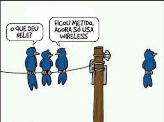 Ilustração. Três pássaros azuis estão pousados em uma extensão do cabo de aço preso a um poste elétrico. À direita, a uma certa distância, está  um pássaro também azul, sozinho, pousado no ar, com a cara virada em direção oposta aos colegas. Um deles questiona: O que deu nele? O outro explica: Ficou metido. Agora só usa wireless.