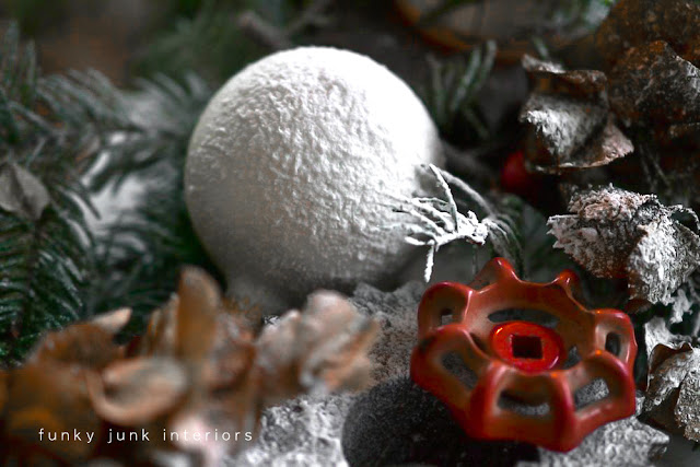 spray snow on a Christmas ornament with red faucet handle in a Christmas centrepiece