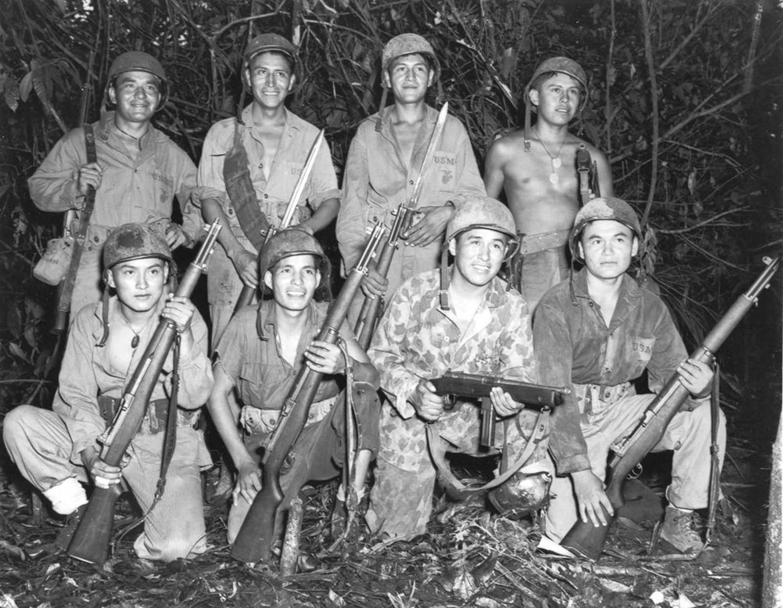Code talkers with a Marine signal unit on Bougainville. Front row, left to right: Privates Earl Johnny, Kee Etsicitty, John V. Goodluck, and Private First Class David Jordan. Back row: Privates Jack C. Morgan, George H. Kirk, Tom H. Jones, and Corporal Henry Bake, Jr. December, 1943.