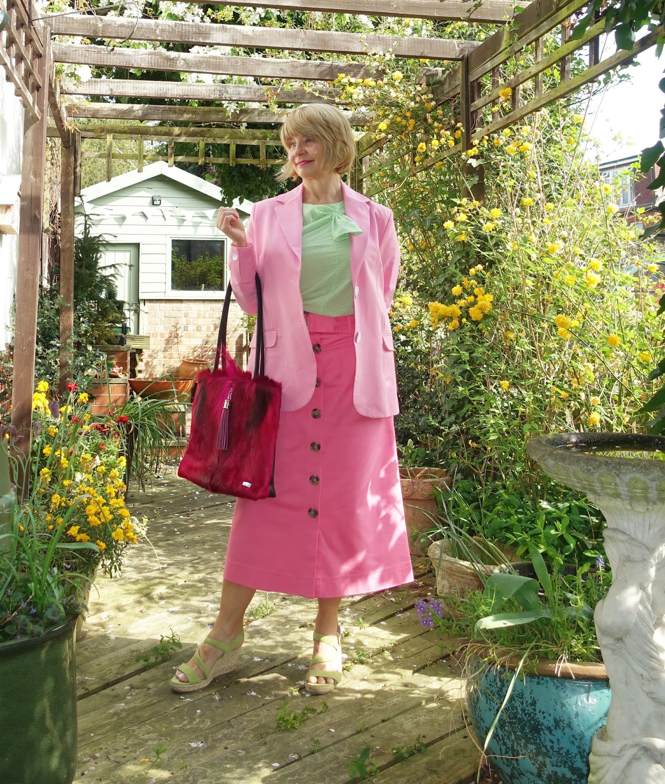 Different shades of pink worn together: midi skirt with jacket and light green top and wedges with a statement deep pink tote bag