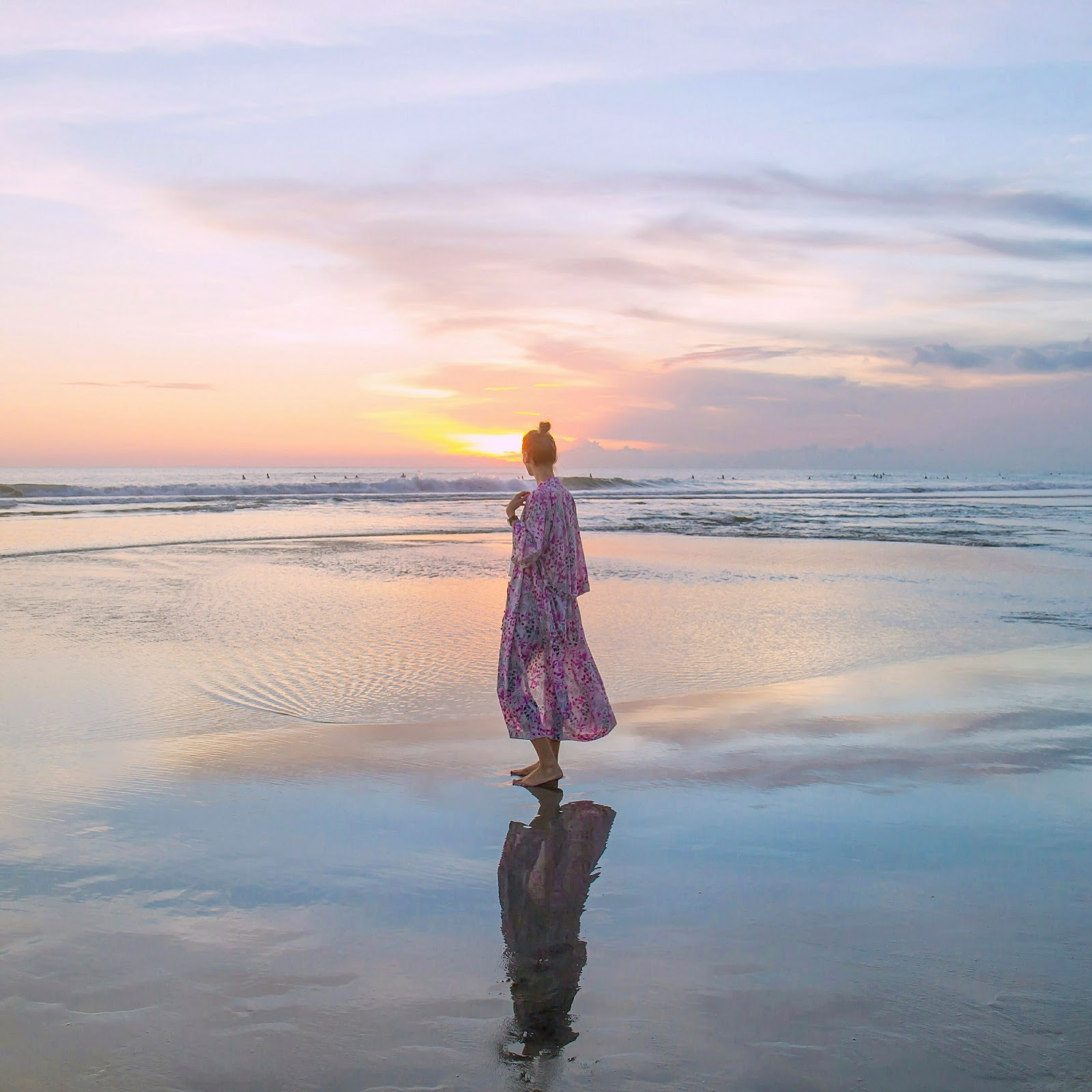 Fashion and travel blogger, Alison Hutchinson, wearing a pink Kayvalya kimono at sunset in Bali, Indoneisa