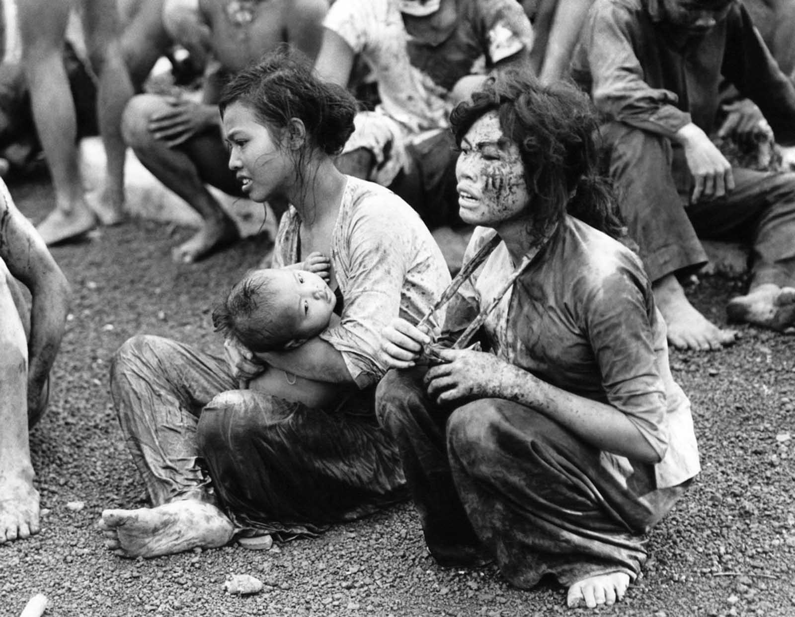 Wounded and shocked civilian survivors of Dong Xoai crawl out of a fort bunker on June 6, 1965, where they survived murderous ground fighting and air bombardments of the previous two days.