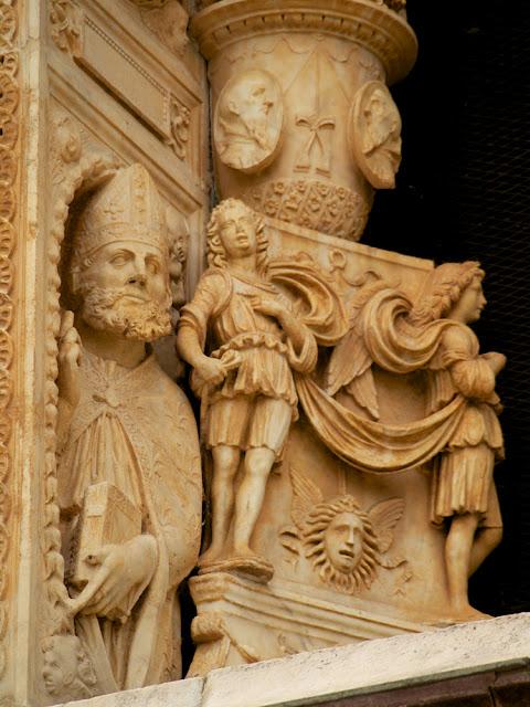 Figuras en la ventana de la fachada de la Cartuja de Pavía