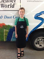 A little pro wearing an A Cleaner World Apron