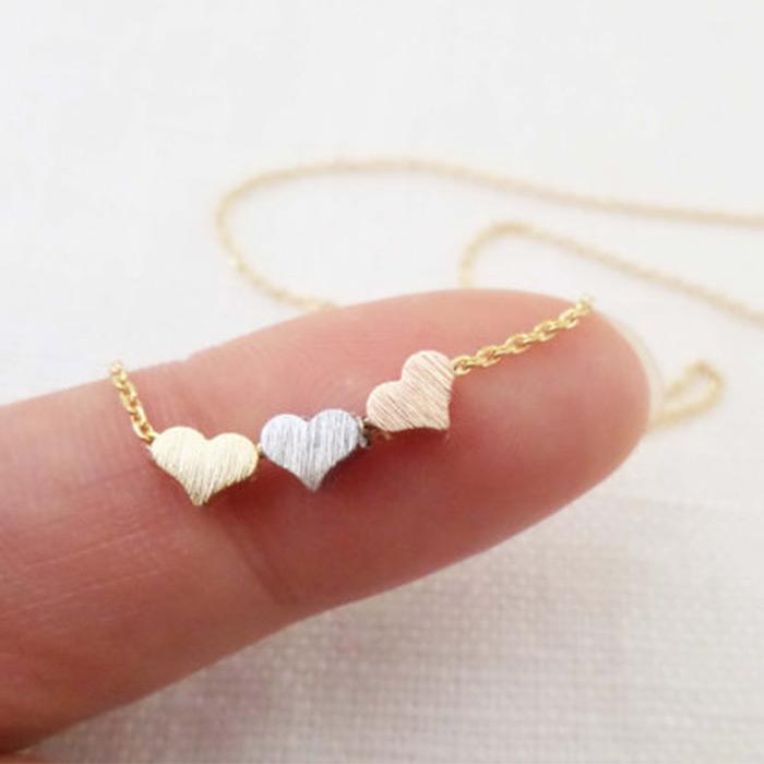 Colar com três corações pequenos texturizados como pngentes.