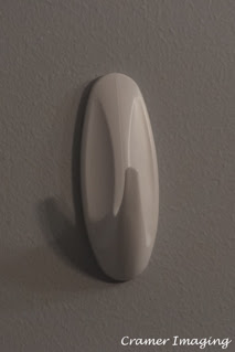 Photograph of a command strip brand white wall hook hanging on the white wall background by Cramer Imaging
