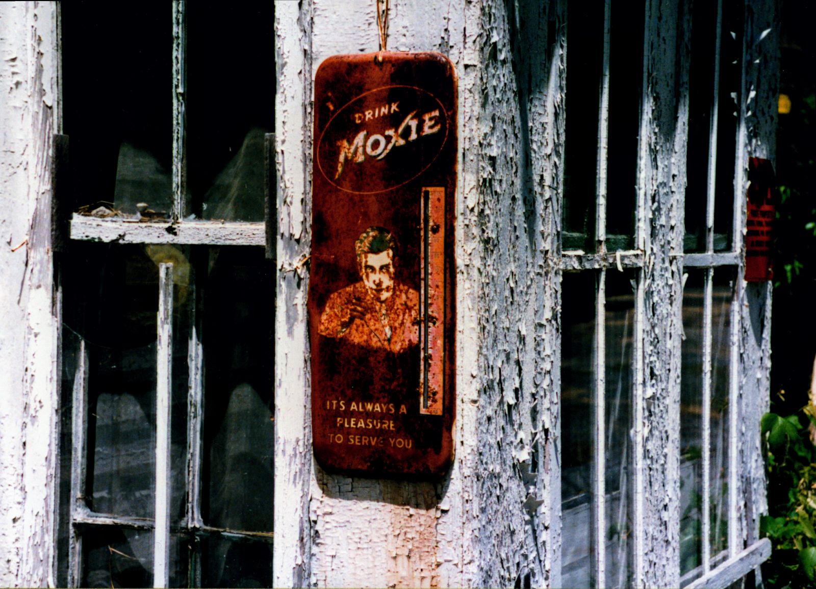 rusted moxie branded thermometer on an old farmhouse window