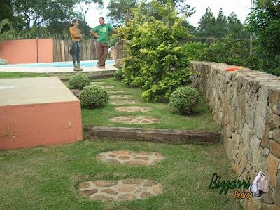 Muro de pedra rústica com os caminhos de pedra no jardim com o degrau de dormente de madeira e a execução do paisagismo em sítio em Mairiporã-SP.