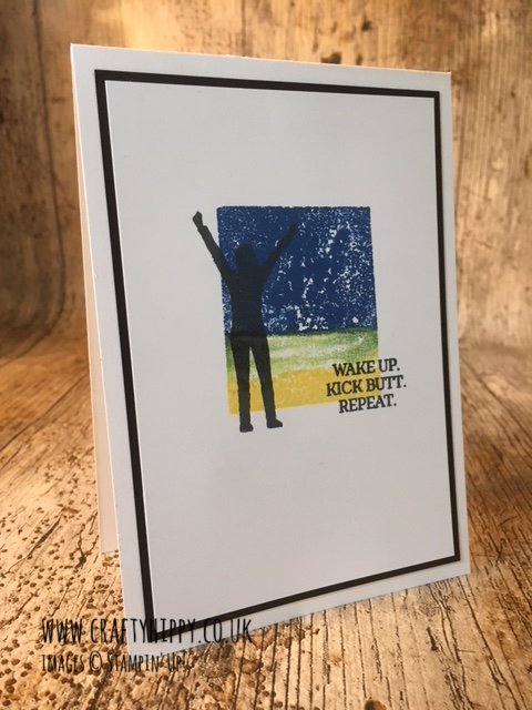 "This image shows a handmade card with the silhouette of a man with outstretched arms in front of a coloured background, and the words ""wake up, kick butt, repeat"" and is made using the Enjoy Life stamp set from Stampin' Up!"