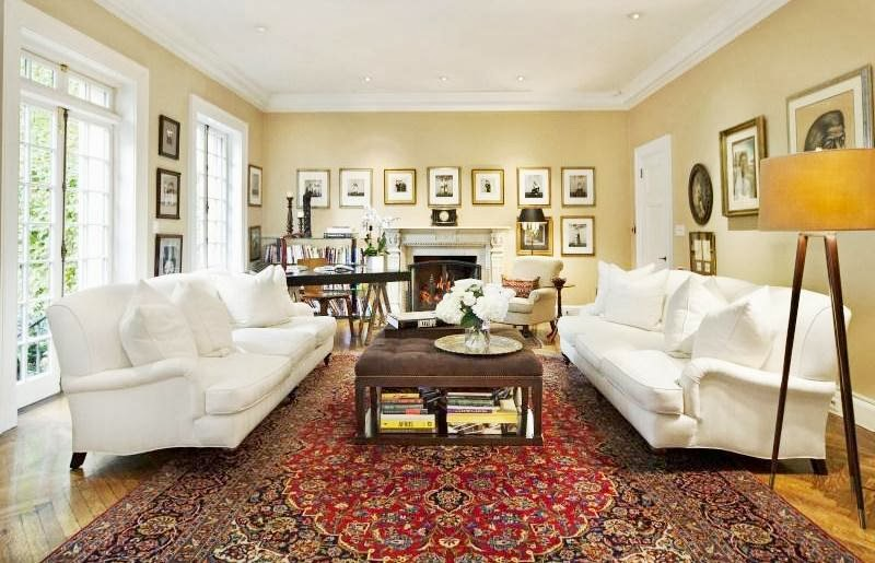 Den in NYC home with white dueling sofas, Persian rugs and herringbone wood floor