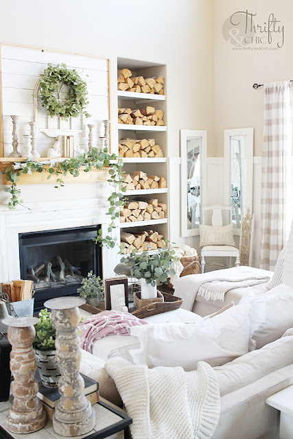 living room with white couch, large window, stacked wood, and shiplap mantel