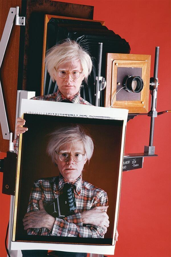 Andy Warhol holding a Polaroid of Andy Warhol. By Bill Ray, 1980