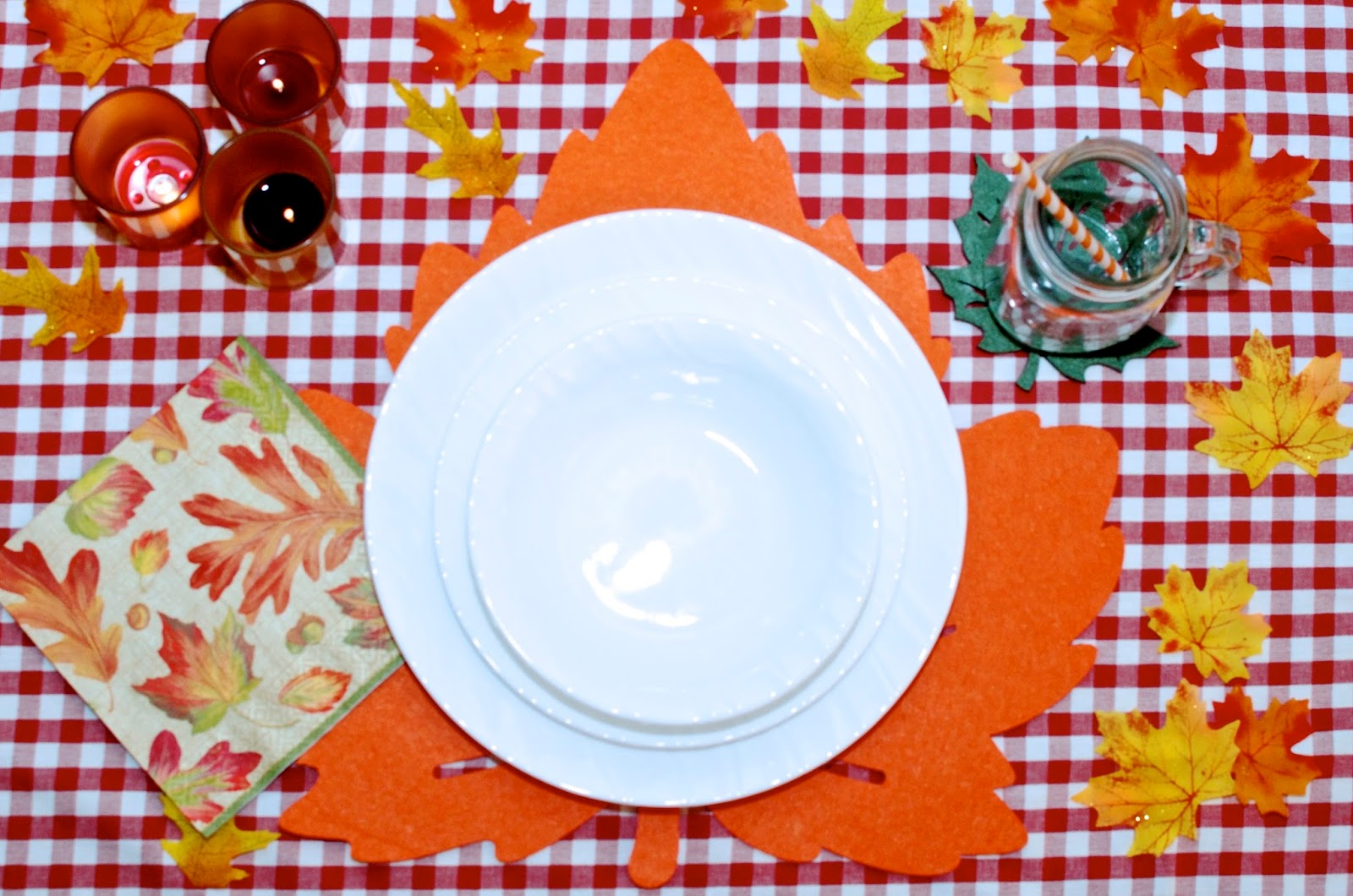 Candles, gingham tablecloth, napkins, leaves, place setting, white dishes and leave placemat