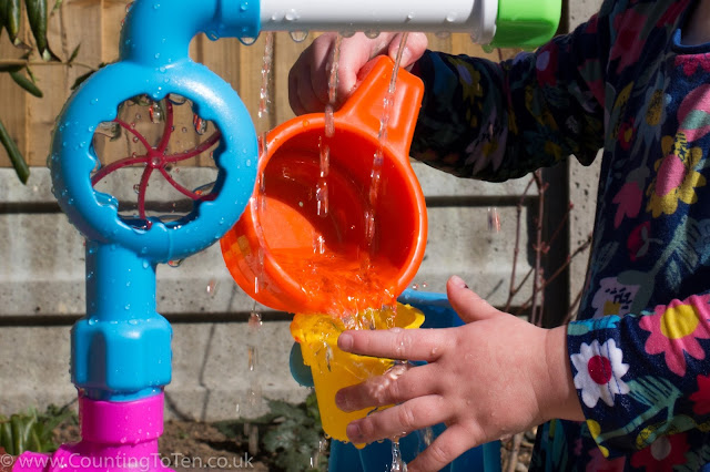 close up of pouring water from an orange cup into the dumper bucket