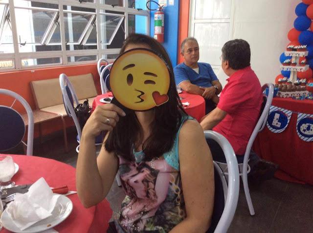 Eu em uma foto segurando uma carinha de emoji feliz