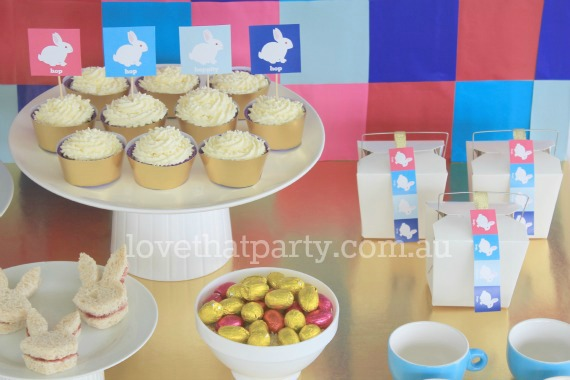 image of pink, blue and turquoise printable Easter bunny cupcake toppers on cupcakes at Easter party table