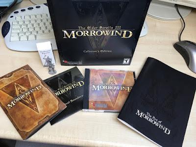 Vor einer alten Tastatur steht der schwarze Morrowind Karton. Davor liegen die Spiele-CD, der Soundtrack, die Anleitung und ein Artbook.