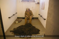 Museum display of prisoner picking oakum in a cell.