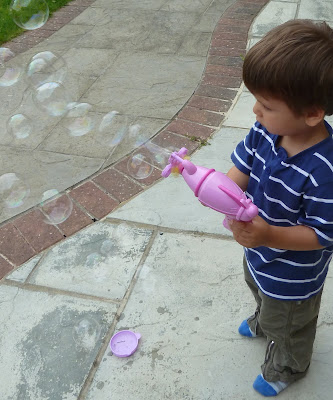 Toddler blowing bubbles in the garden