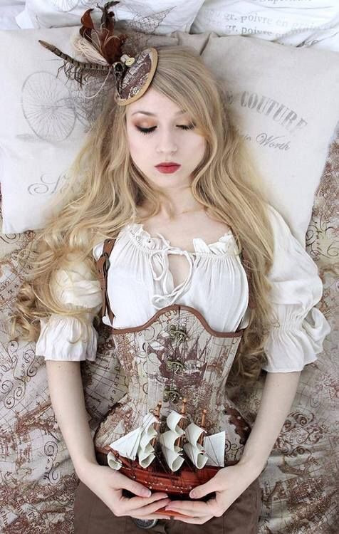 A Steampunk outfit with a corset, blouse, and fascintor/hat. The woman looks like a Steampunk Sleeping Beauty as she lies on pillows with her eyes shut, holding a small wooden ship.