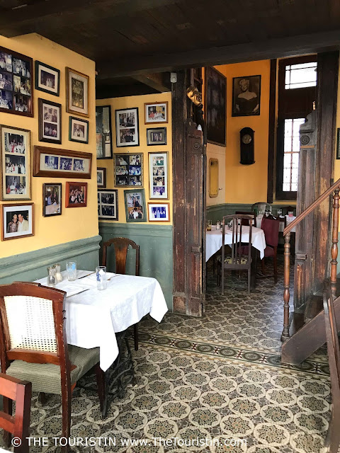 Interior and with photos decorated walls and tiled floor at restaurant La Guarida in Havana in Cuba