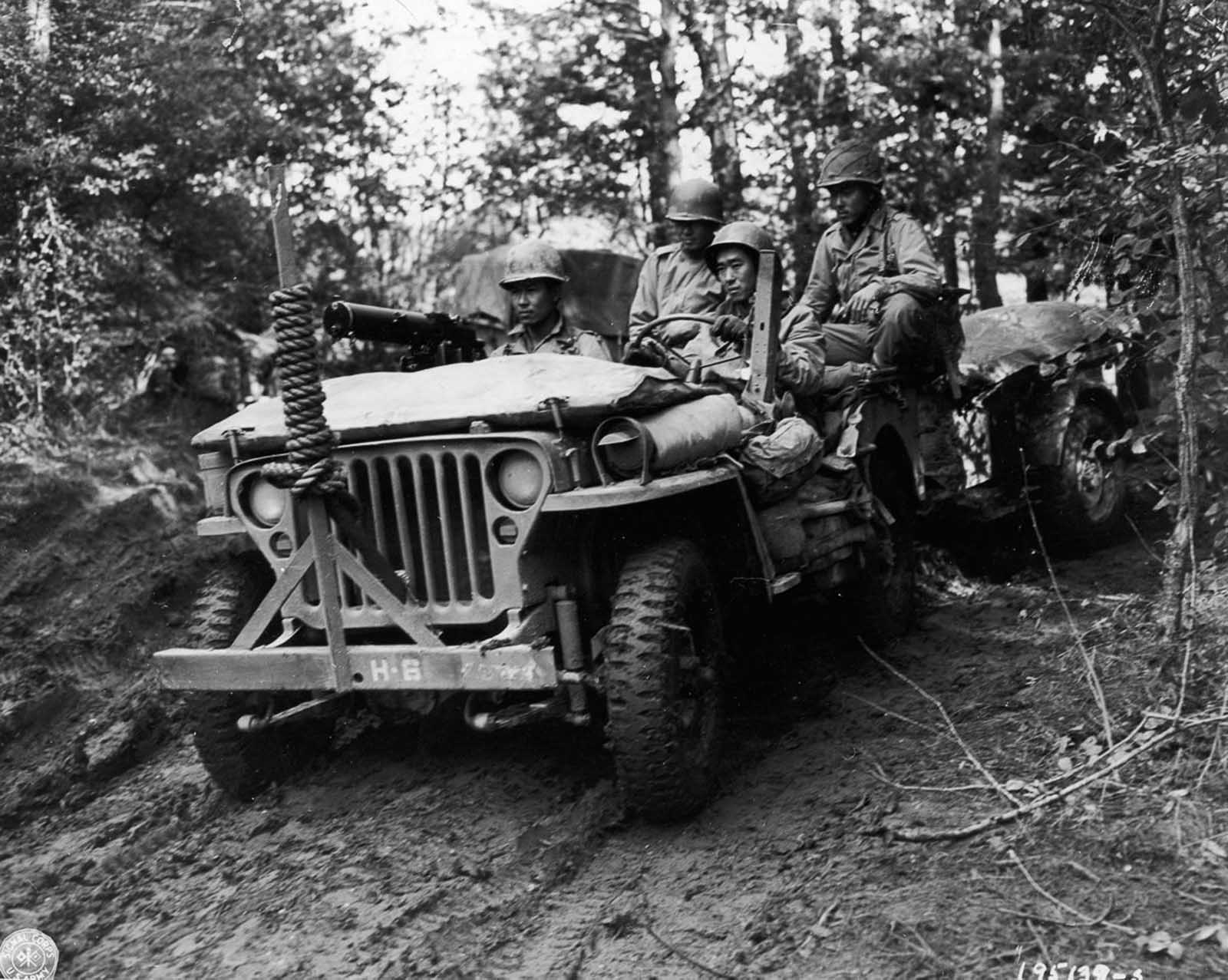 Soldier drive a Jeep towing a supply trailer in rural France. October 1944.