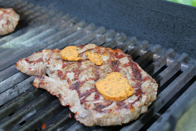 Steaks on the grill topped with chili-lime butter