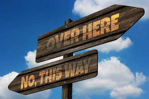 """Duas placas de madeira apontam para direções opostas: """"por aqui""""; """"não, por ali""""."""