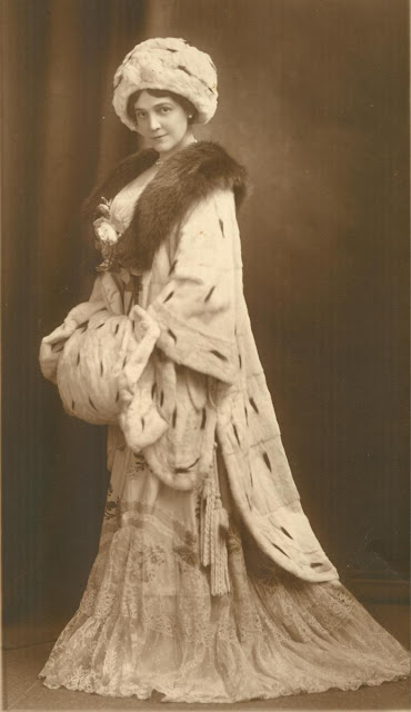 Mable poses for a full length portrait in spotted furs, a fur hat and a flowing dress.