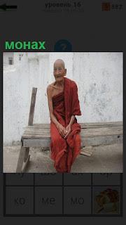 На скамейке сидит одинокий монах в национальной одежде