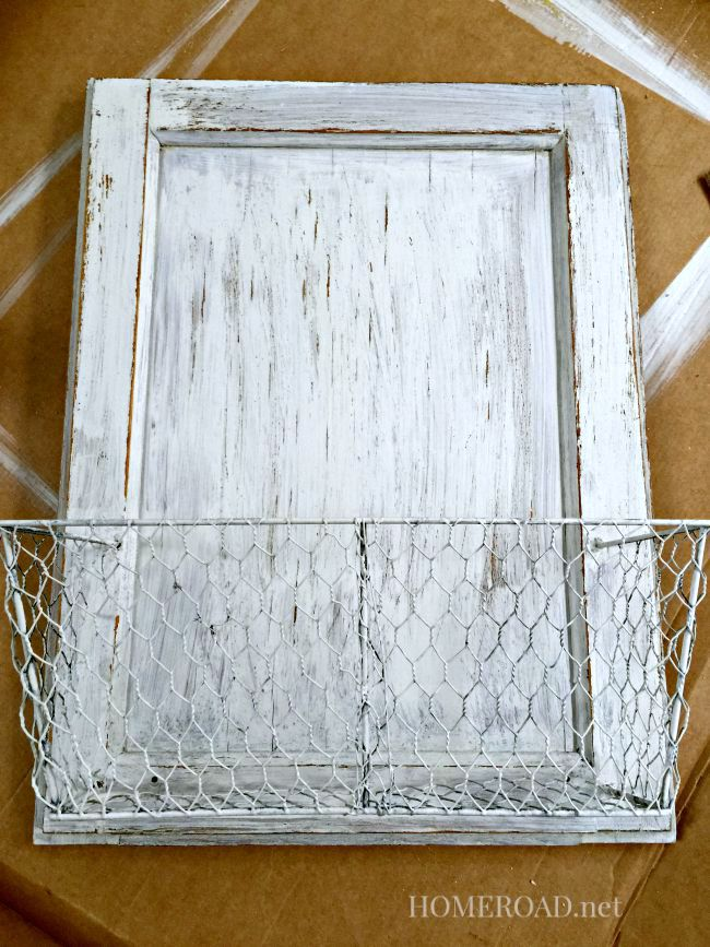 Distressed cabinet door with white basket attached