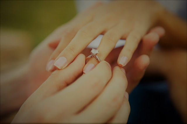 K'Mich Weddings - wedding planning - engagement tips - man placing ring on woman's finger