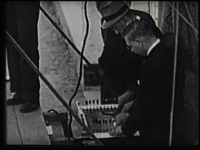 A black and white photograph of two men bent over a switchboard.