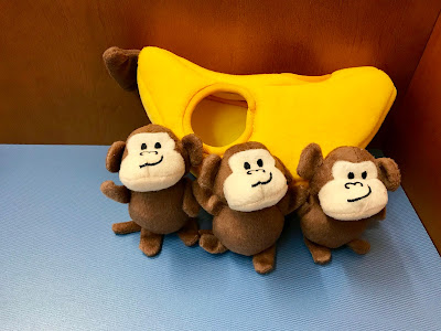 Three small monkeys with a large yellow banana