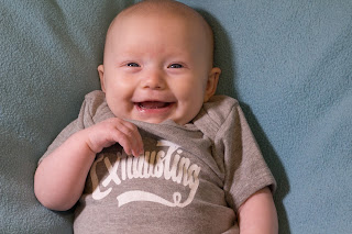 "A baby in an ""exhausting"" vest giving a big smile"
