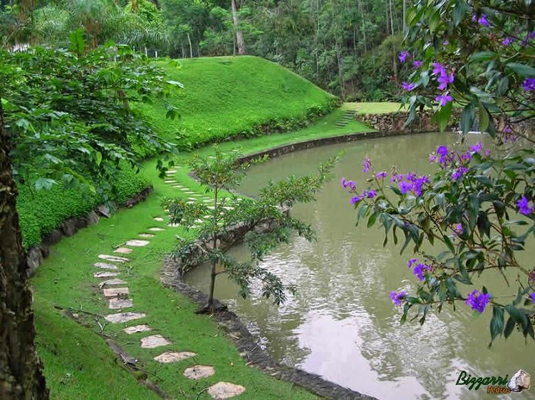 Caminho com pedra santo mé em volta da construção do lago com os muros de pedra rústica e a execução do paisagismo sendo no talude com grama amendoim.